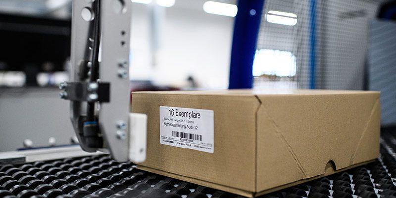 Barcode-Etikett wird auf einen Karton appliziert
